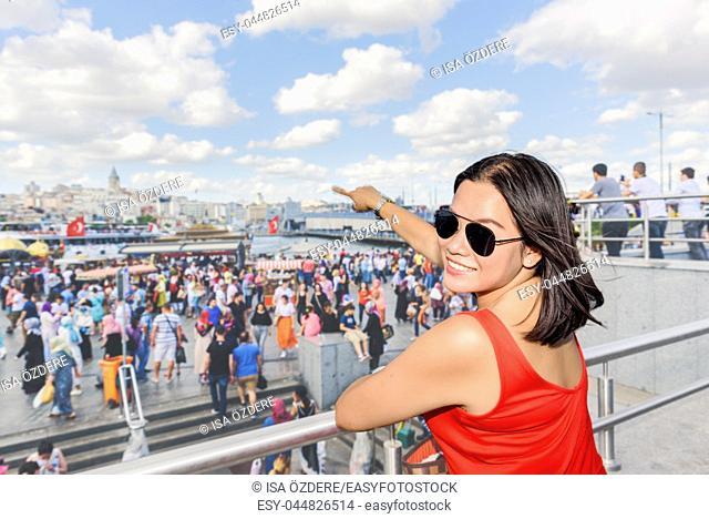Beautiful Chinese woman shows Galata Tower at Eminonu district in Istanbul,Turkey
