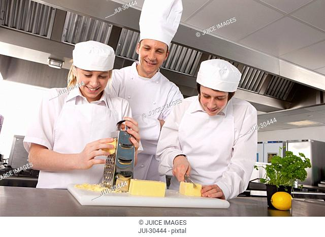 Chef watching trainees grate and slice cheese in commercial kitchen