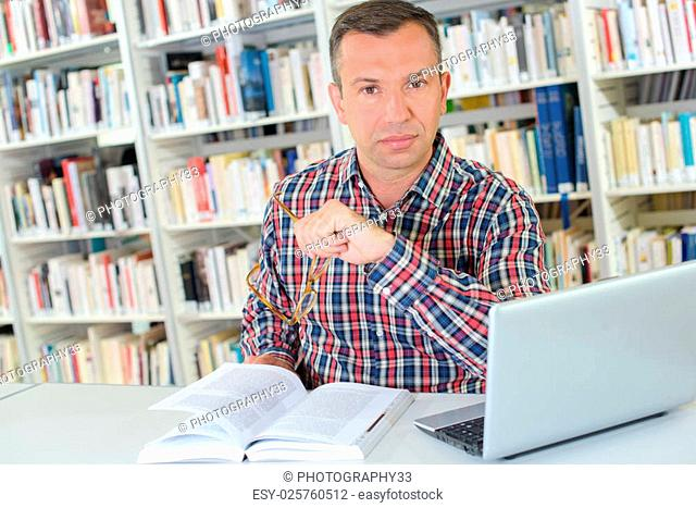 Man in library with book and laptop