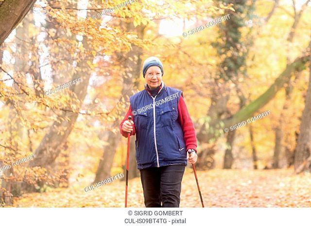 Senior woman nordic walking in park