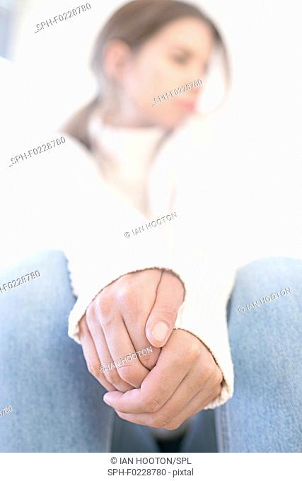 Young woman with hands clasped