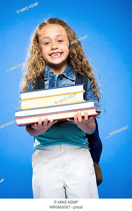 Smiling girl with backpack holding hardcover books