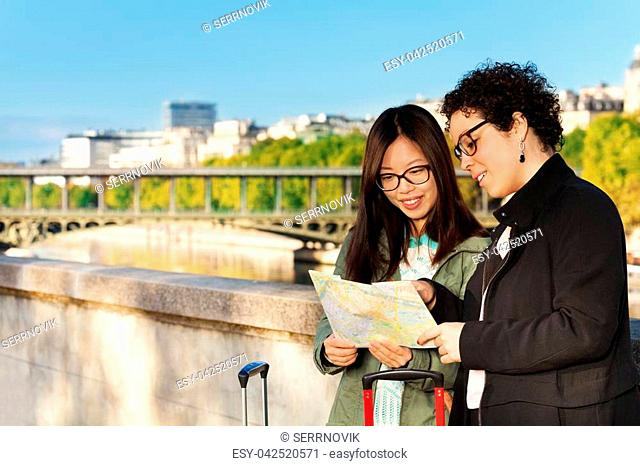 Two young attractive women with suit cases reading map at the embankment of the Seine River