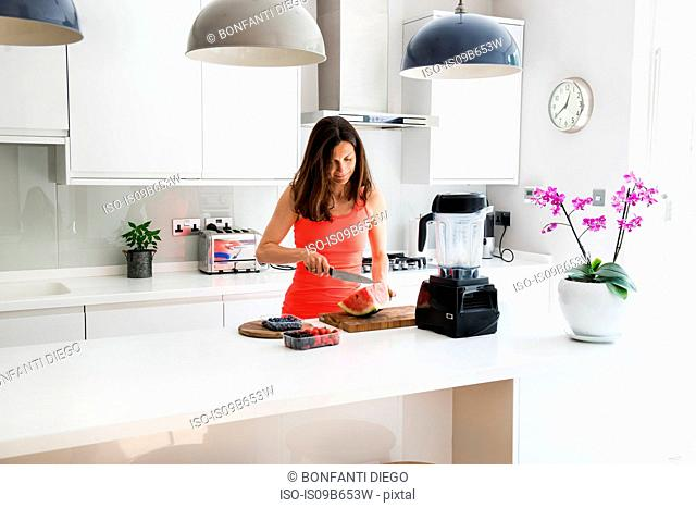 Woman chopping watermelon, preparing smoothie in blender