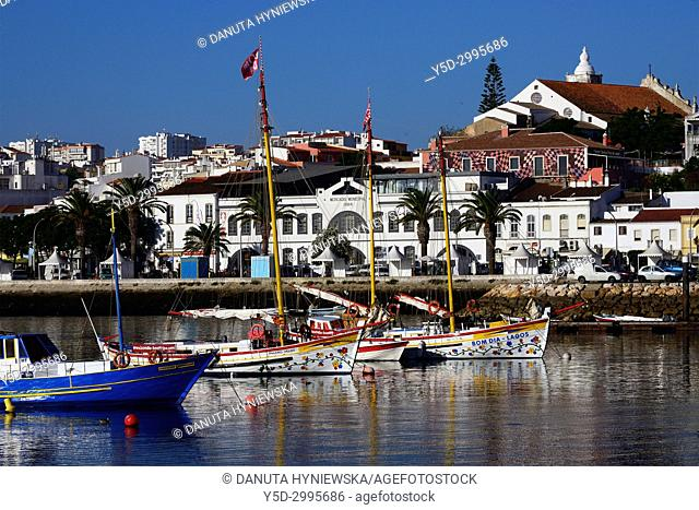 Boats moored in the harbour, in background old town with historic food market, Ciencia Viva - cultural center and Sao Sebastiao church, Lagos, Algarve, Portugal