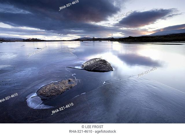Winter view of Loch Ba' at dawn, loch partly frozen with two large rocks protruding from the ice, calm morning, Rannoch Moor, near Fort William, Highland