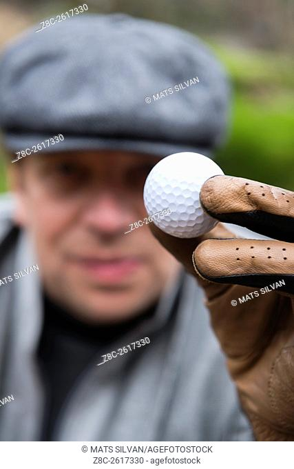Golfer with flat cap and a glove holding up a golf ball in Ascona, Switzerland