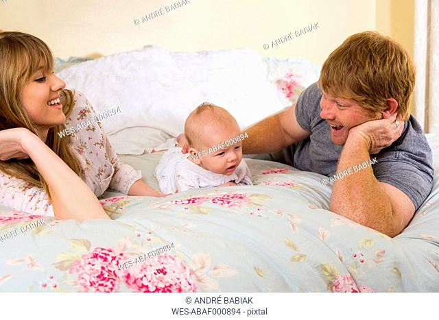 Parents with baby boy on bed, smiling