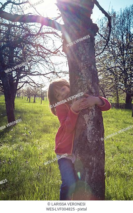Portrait of smiling little girl embracing tree