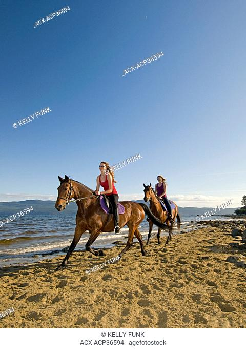 Two young women enjoy a horesback ride at a beach near Powell river on the upper Sunshine coast, Vancouver and coast mountain region, British Columbia, Canada