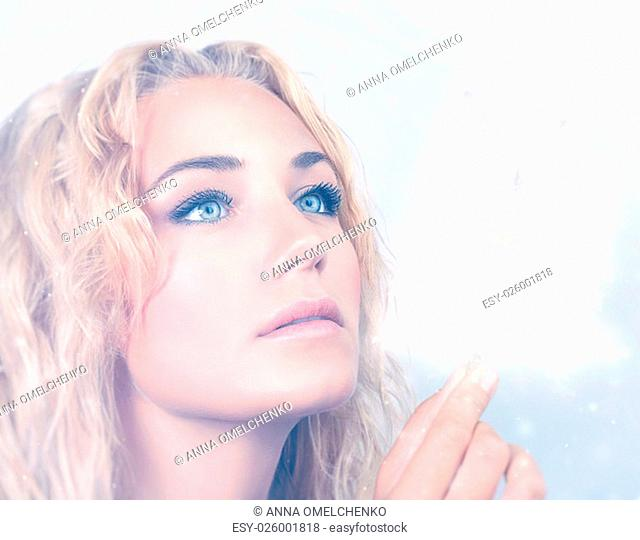Closeup portrait of beautiful blond woman holding in hand magical glowing snowflakes, with wonder looking on Christmas miracle