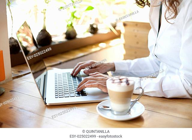woman with white shirt typing on keyboard pc laptop and cappuccino coffee cup ready thinking on light brown wooden table
