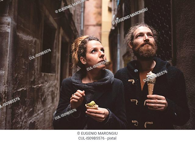 Couple with gelato in dark alley, Venice, Italy