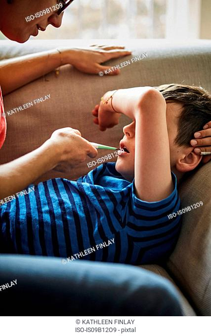 Mother taking son's temperature with digital thermometer