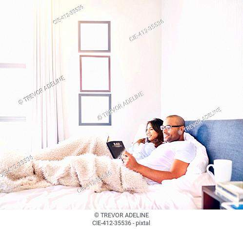 Smiling couple relaxing, reading book in bed