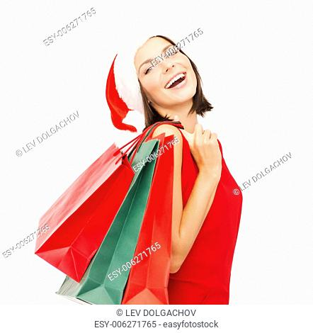 sale, gifts, christmas, x-mas concept - smiling woman in red dress and santa helper hat with shopping bags