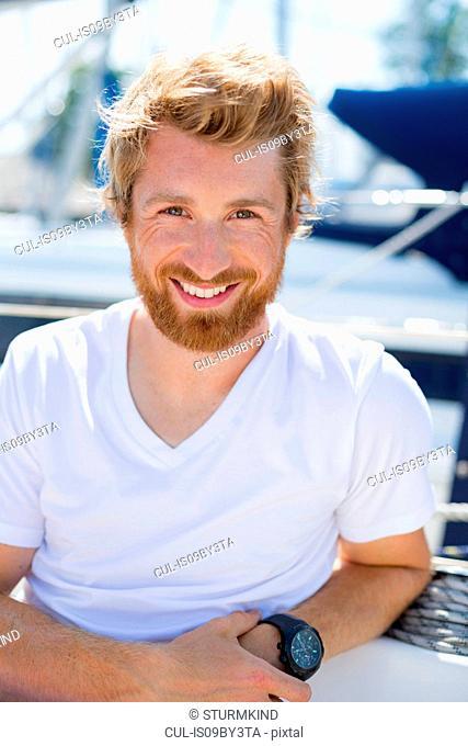 Young man on sailboat at Chiemsee lakeside, portrait, Bavaria, Germany