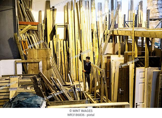 Interior view of warehouse with stacks of wooden planks, young man working