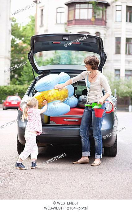 Germany, Leipzig, Mother and daugher 4-5 loading luggage into car