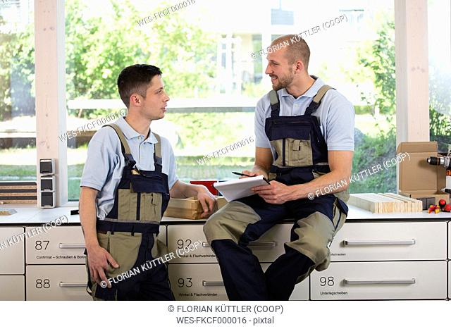 Two craftsmen in workshop talking