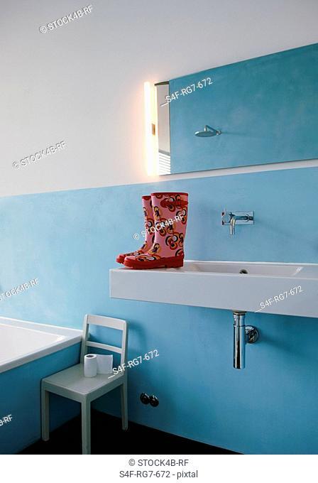 Wellington boots on sink in bathroom