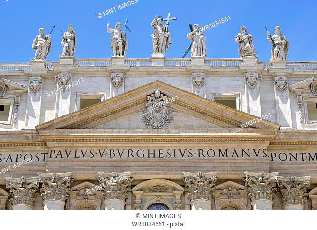 St Peter's Basilica in Rome, Italian Renaissance architecture, and UNESCO world heritage site. Facade with columns, inscription and statues of religious figures...
