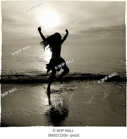 Little girl dancing on the ocean shoreline