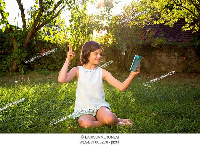 Girl sitting on a meadow taking selfie with tablet