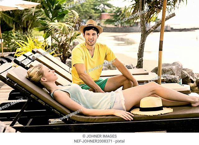 Young couple resting on deckchairs