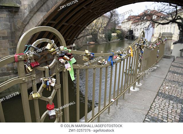 Love locks on railing by canal; Prague, Czech Republic