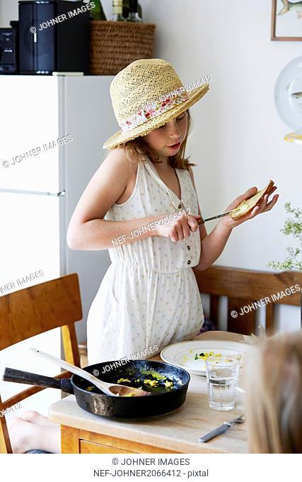 Girl applying butter on bread