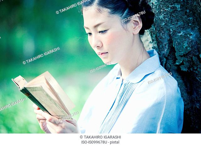 Young woman reading book, close up