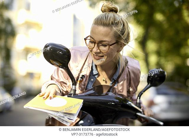Woman looking to city tour guide map, sitting on motor scooter, in Berlin, Germany