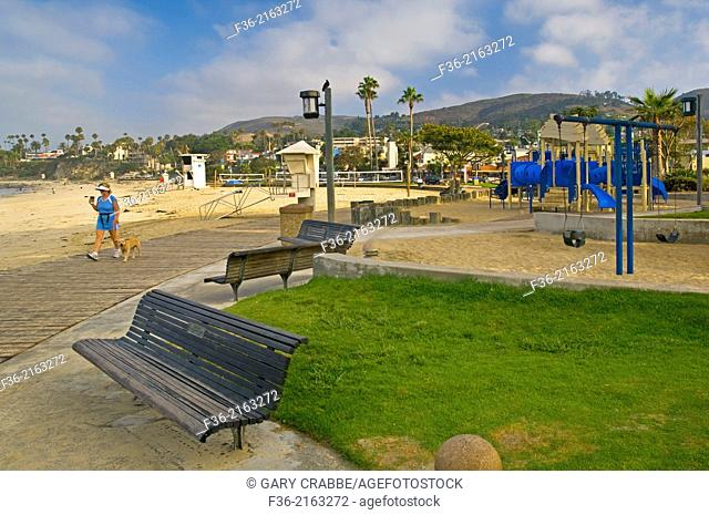 Woman walking her dog holding coffee on boardwalk next to sand at Laguna Beach, Orange County, California