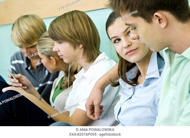 Teenagers sitting on school hallway