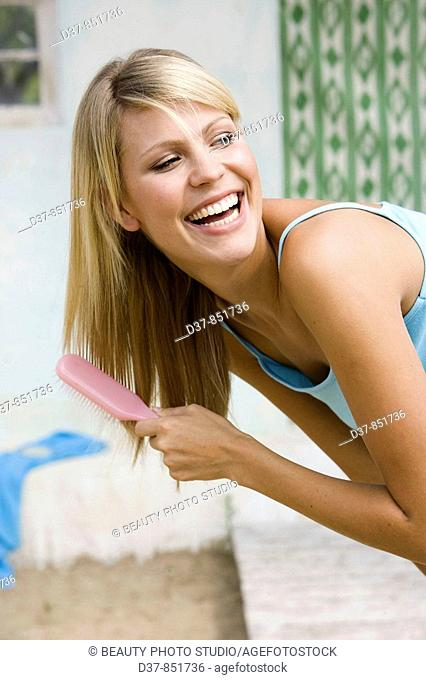 Woman brushing her hair happy