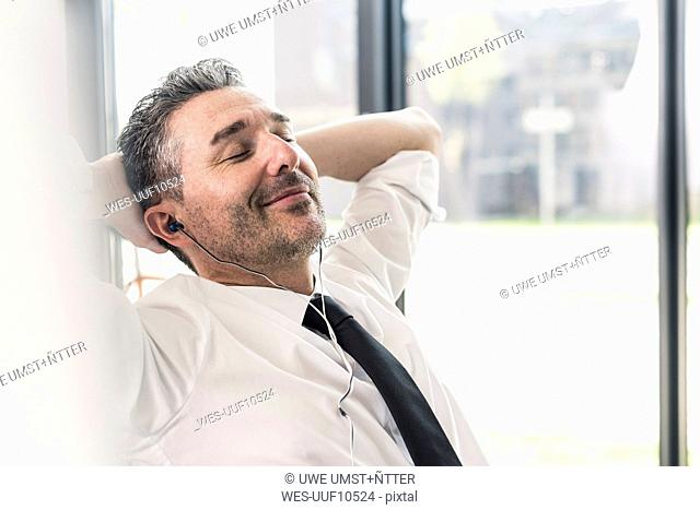 Portrait of smiling businessman with eyes closed listening music with earphones