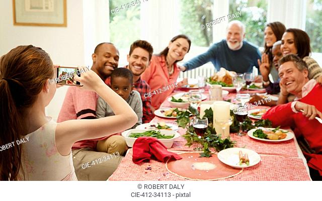 Girl with camera phone photographing multi-ethnic family at Christmas dinner table