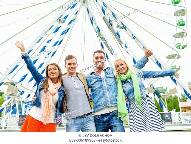 leisure, amusement park and friendship concept - group of smiling friends waving hands with ferris wheel on the back