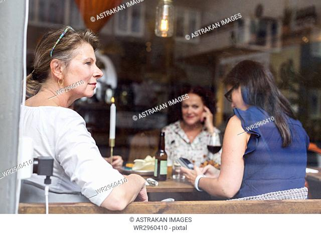 Businesswomen talking during lunch in restaurant, one woman looking through window