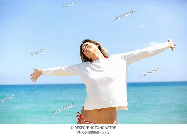Pretty blonde woman enjoying at the beach with arms opened