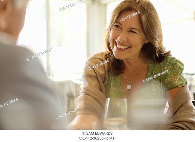 Smiling mature woman enjoying date, dining at restaurant