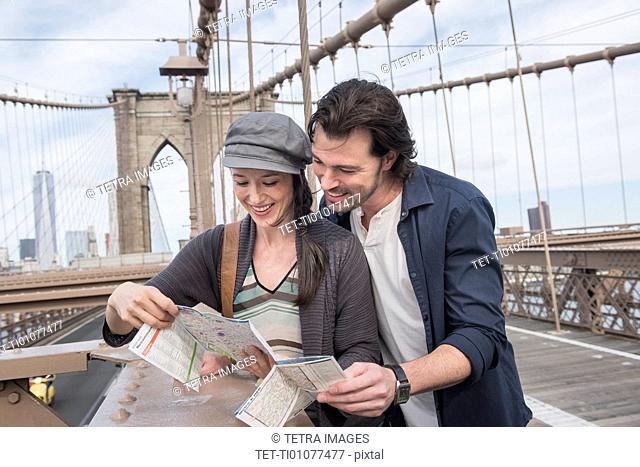 Happy couple reading map on Brooklyn Bridge