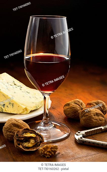 Still life with red wine, nuts and cheese