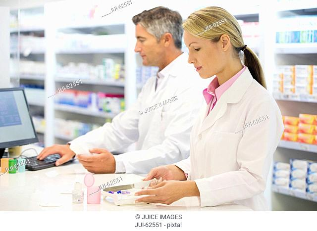 Pharmacist counting pills at pharmacy counter