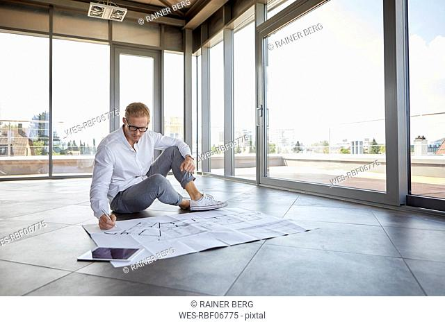 Young man sitting in empty room with panorama window working on blueprint