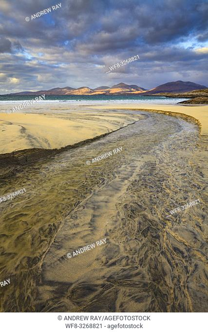 The stream on Luskentyre Beach on the Isle of Harris, with the hills of North Harris in the distance captured on a stormy afternoon in late October
