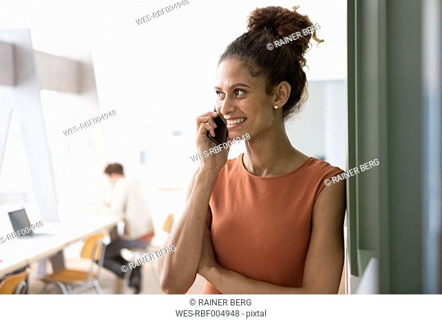 Smiling woman in office on cell phone