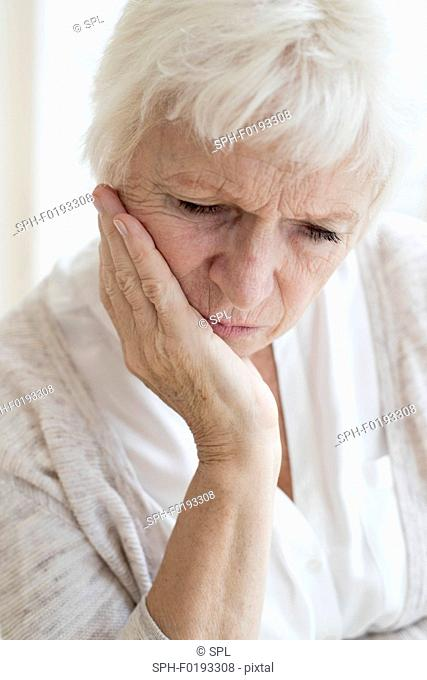 Senior woman with hand on chin