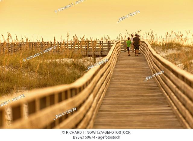 A scenic view of a boardwalk thru the sand dunes at the Gulf Coast State Park's white sand beach, in Orange Beach, Alabama
